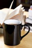 在黑杯子和开放书堆的咖啡 免版税库存照片