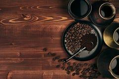 在黑杯子的热的咖啡和土耳其罐cezve用豆,有拷贝空间的茶碟在棕色老木板背景,顶视图 库存照片