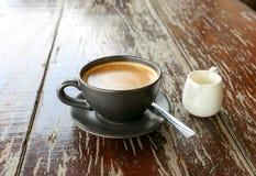 在黑杯子的热的拿铁咖啡在木桌上 库存图片