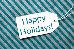 在绿松石包装纸的标签,发短信节日快乐 免版税库存图片
