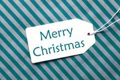 在绿松石包装纸,文本圣诞快乐的标签 免版税库存照片