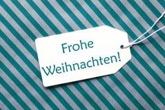 在绿松石包装纸, Frohe Weihnachten的标签意味圣诞快乐 库存照片
