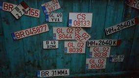 在绿松石木墙壁上的老和新的牌照收藏 免版税图库摄影