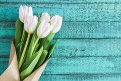 在绿松石木桌面的浅粉红色的郁金香花束与拷贝空间 库存照片