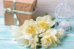 黄水仙在绿松石的花、蜡烛和礼物盒绘了木头 免版税图库摄影