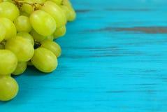 在绿松石的鲜绿色的葡萄困厄了木背景 库存照片