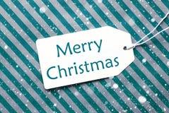 在绿松石纸,雪花,文本圣诞快乐的标签 免版税图库摄影