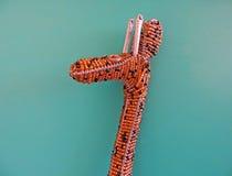 在绿松石背景的祖鲁族人串珠的长颈鹿装饰品 免版税库存图片