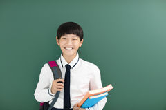 在黑板前的微笑的少年学生女孩立场 免版税库存图片