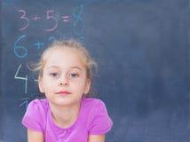 在黑板前面的年轻白肤金发的白种人女孩 免版税库存照片