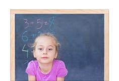 在黑板前面的年轻白肤金发的白种人女孩 免版税库存图片