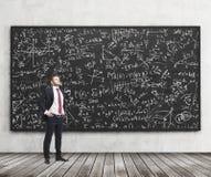 在黑黑板前面站立算术惯例有很多一个确信的年轻人的侧视图 分析家的概念在 库存图片
