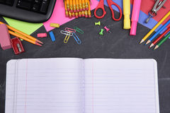 在黑板和开放笔记本的学校用品 免版税库存图片