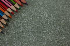 在黑板安排的各种各样的颜色铅笔 库存照片