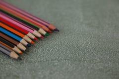 在黑板安排的各种各样的颜色铅笔 库存图片