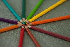 在黑板安排的各种各样的颜色铅笔 免版税库存照片