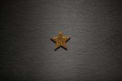 在黑板岩纹理背景的一个金黄星 免版税库存照片