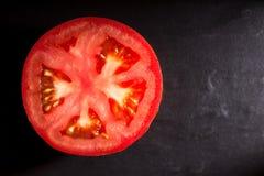 在黑板岩背景的蕃茄 库存照片