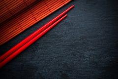 在黑板岩,食物后面的日本红色筷子和竹席子 免版税库存图片