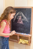 在黑板的小女孩凹道 库存图片