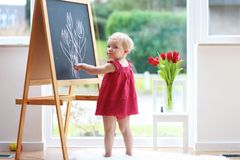 在黑板的小女孩图画 免版税库存照片