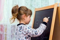 在黑板的小的美丽的女孩图画 免版税库存图片