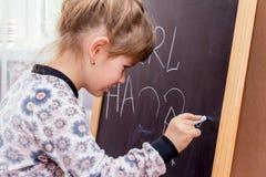 在黑板的小的美丽的女孩图画 库存图片