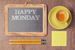 在黑板的愉快的星期一文本有咖啡杯的 在视图之上 库存照片