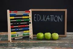 在黑板的教育文本有算盘和绿色苹果的 图库摄影