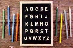 在黑板的木英语字母表A-Z 在wo的颜色铅笔 库存照片