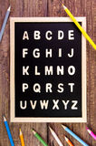 在黑板的木英语字母表A-Z 在wo的颜色铅笔 免版税库存图片
