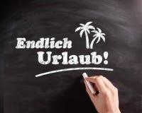 在黑板的概念性Endlich Urlaub文本 库存图片
