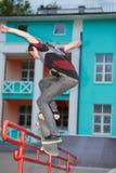 在滑板的男孩火车在晚上skatepark 库存图片