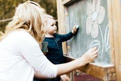 在黑板的美丽的母亲和儿子图画有白垩的 免版税库存照片