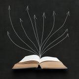 在黑板背景的被打开的书 免版税库存照片