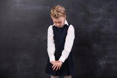 在黑板附近的哀伤的矮小的女小学生 免版税库存图片