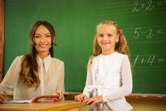 在黑板附近的小女小学生 图库摄影