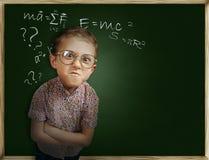 在黑板附近的情感学生男孩 免版税库存图片