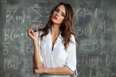 在黑板附近的年轻性感的女老师在性姿势 图库摄影