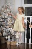 在结构树附近的圣诞节女孩 库存照片