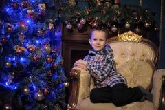 在结构树附近的男孩圣诞节 免版税库存照片