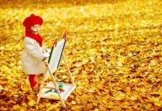 在画架的儿童图画在秋天公园。创造性的孩子发展 免版税库存图片