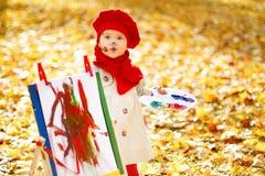 在画架的儿童图画在秋天公园。创造性的孩子发展 免版税图库摄影