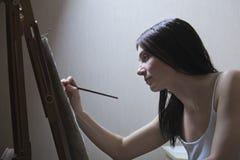 在画架的妇女绘画 免版税库存照片
