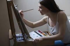 在画架的妇女绘画 库存图片