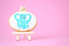 在绘画画架的姜饼大象在与拷贝空间的桃红色 图库摄影