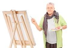 在画架的成熟艺术家图画 图库摄影