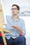 在画架的男性艺术家油漆在车间 免版税库存照片