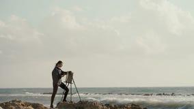 在画架的美丽的女孩图画在海洋的背景 影视素材
