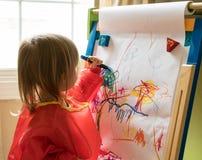 在画架的年轻女婴图画 库存照片
